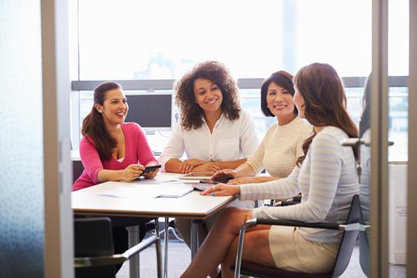 Four women having a meeting in an office