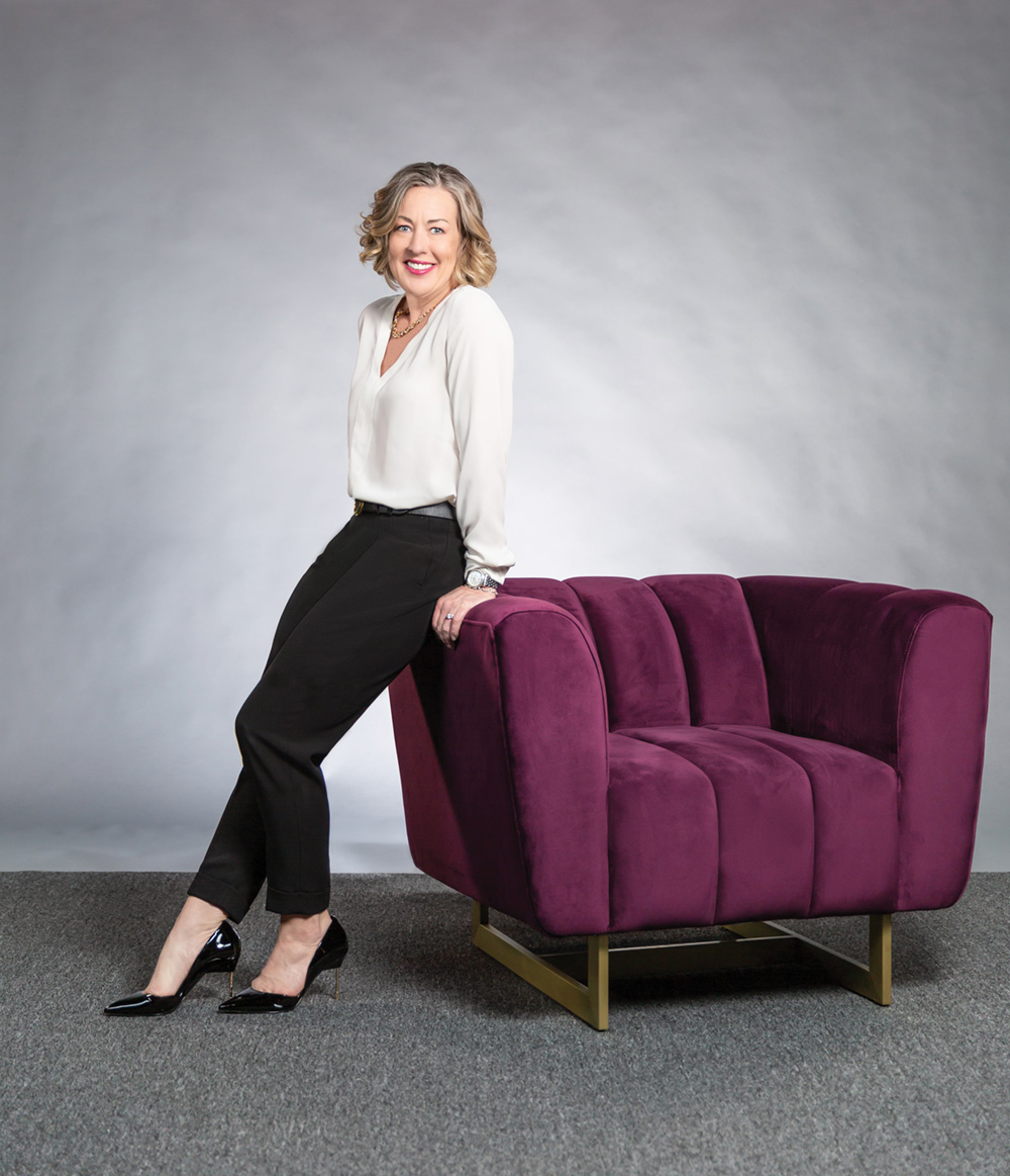 Sue sitting on the arm of a red chair